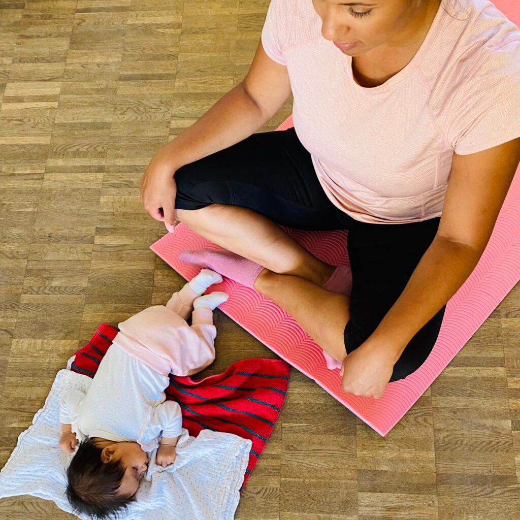 Eine dunkelhäutige Frau im rosa Shirt auf einer rosa Fitnessmatte. Vor ihr liegt ihr dunkelhäutiges Baby mit schwarzen langen Haaren auf einem weißen Spucktuch und rot gestreiftem Handtuch. Beide befinden sich im Rückbildungskurs zur Rückbildung nach der Schwangerschaft. Die Mama wird ihre starke Mitte trainieren, ihren Beckenboden wahrnehmen und ihre Rectusdiastase schließen. Der Kurs findet bei Carmen Hickmann in Emmelshausen bei Mamas in Motion statt.